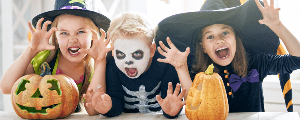 three children doing scary poses for halloween