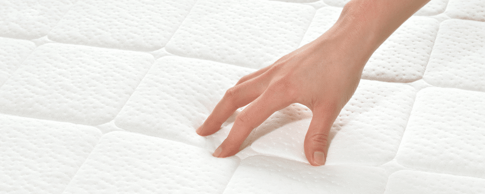 a hand touching the surface of a Custom mattress topper