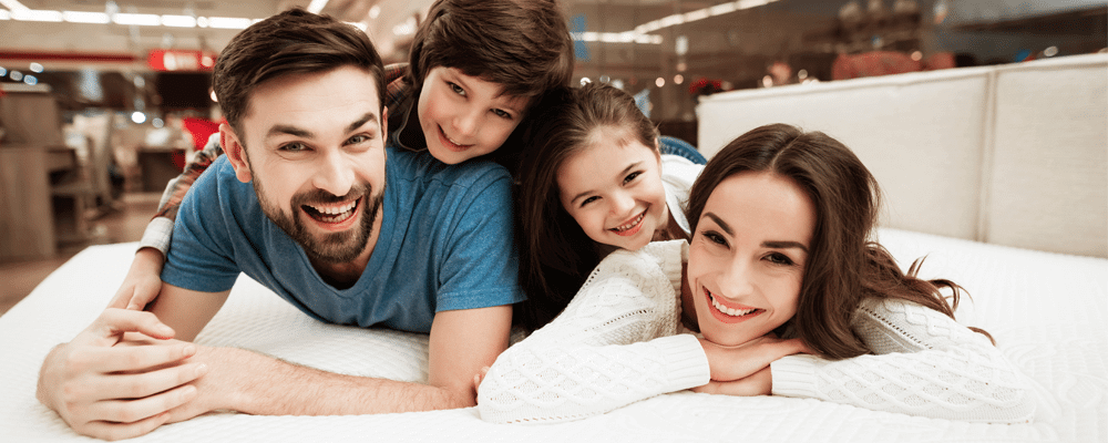 a family lying on a bed enjoying a mattress sale