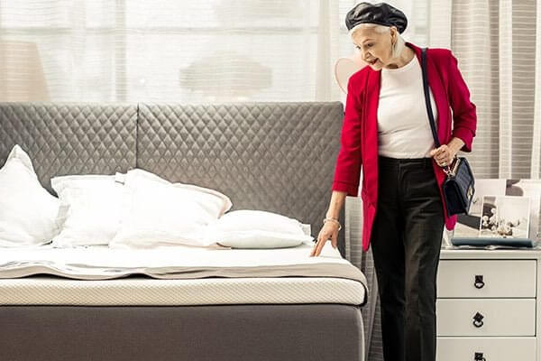 older woman looking at a mattress