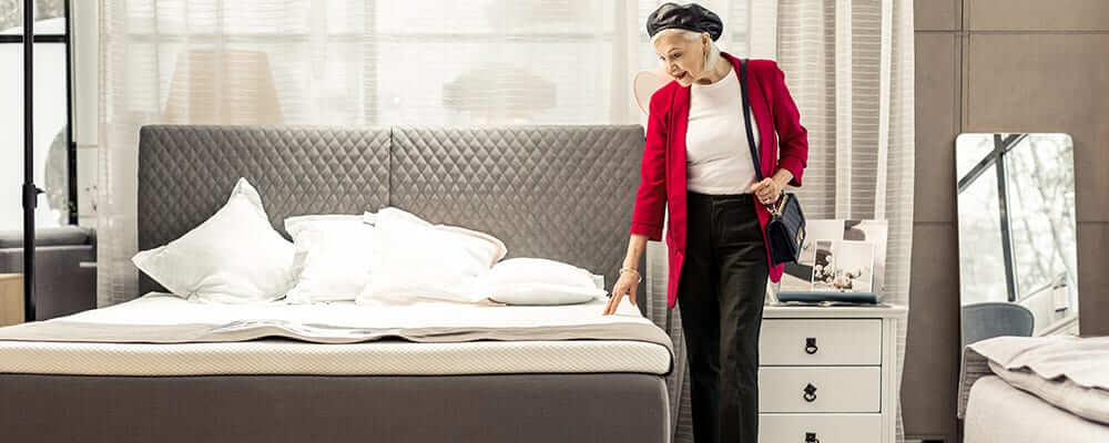 older woman looking at a mattress