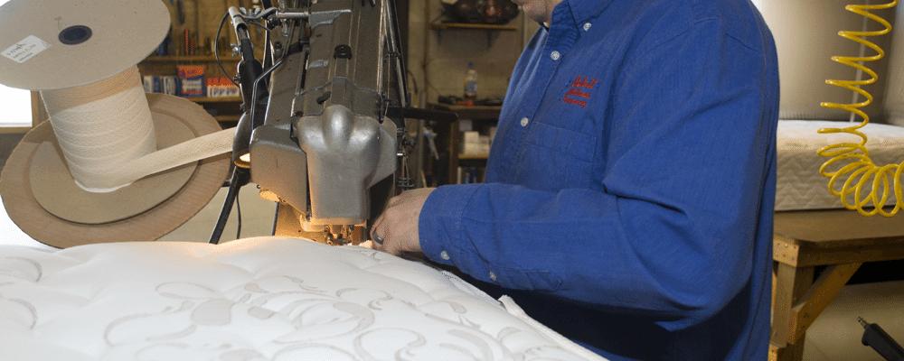 An employee at Beloit Mattress hand making a mattress using quality craftsmanship