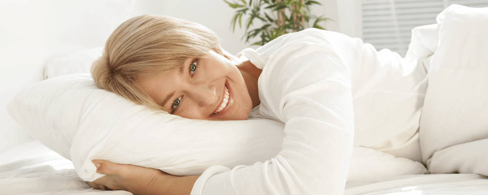 Woman waking up happy after a night of sleep on her pillow top mattress pad