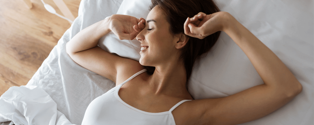 Woman wakes up feeling healthy and re-energized after her first night of sleep on her pillow top mattress pad