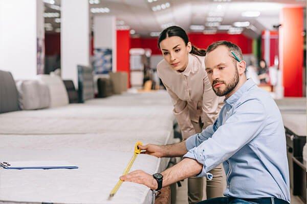 Couple measuring a mattress