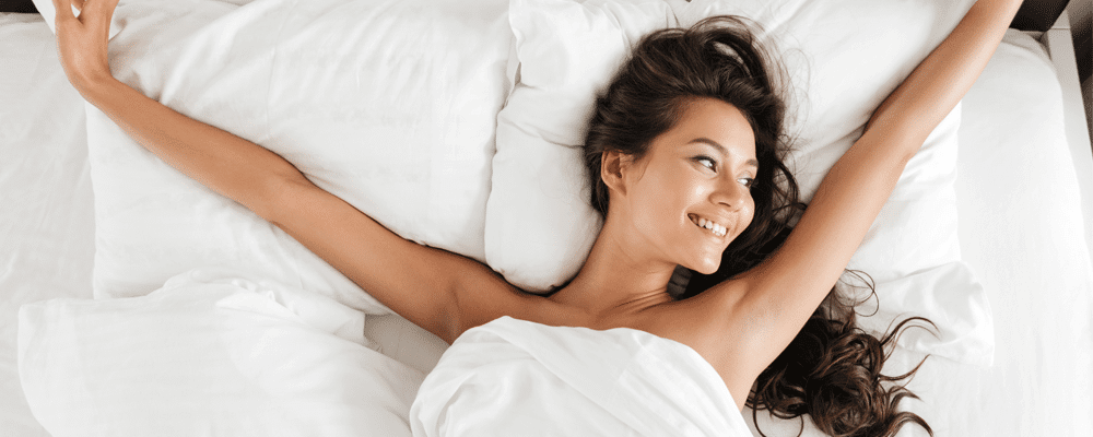 woman waking up and smiling on a white bed