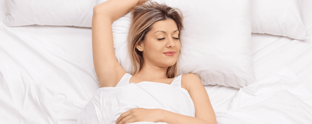 woman smiling while sleeping is the answer of Do mattress toppers work