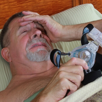 Man frustrated awake CPAP in Bed