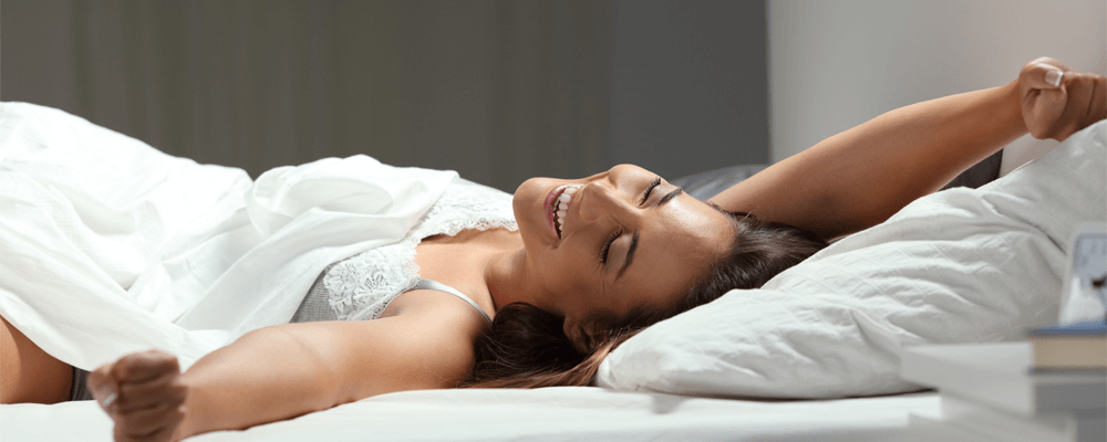 woman waking up happy on the best mattress