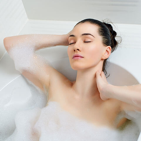 Woman taking hot bath due to Restless Legs Syndrome
