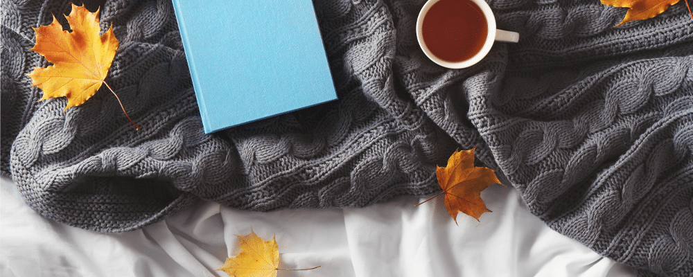 orange leaves are scattered and notebook and coffee mug on top of a mattress