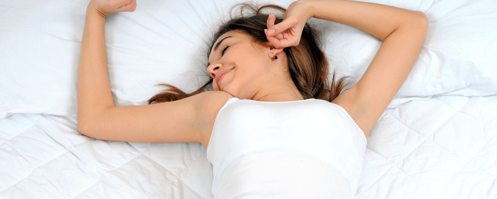 woman is stretching as she wakes up after sleeping on a white mattress