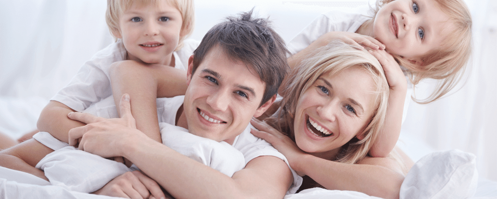 a happy family lying down on their memory foam mattress