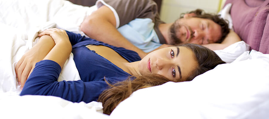 woman in bed with sleeping husband